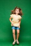 Young pretty girl jumping over green background. Stock Images