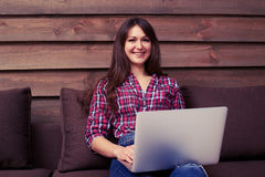 Young pretty girl with laptop working inside while looking at th Royalty Free Stock Image