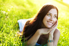 Young pretty girl laying on the grass Royalty Free Stock Photos