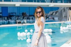 Young pretty girl with long hair and in black sunglasses is standing near pool. She wears gray T-shirt and skirt. She is.  stock photography