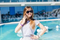 Young pretty girl with long hair and in black sunglasses is standing near pool. She wears gray T-shirt and skirt. She.  royalty free stock photos