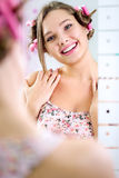 Young pretty girl looking her reflection in mirror Royalty Free Stock Photos