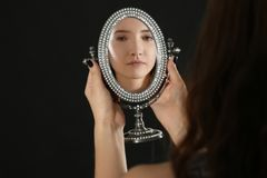 Young pretty girl looking in mirror. On black background Royalty Free Stock Photography