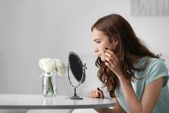 Young pretty girl looking in mirror. At home Stock Image