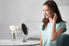 Young pretty girl looking in mirror. At home Royalty Free Stock Images