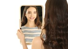 Young pretty girl looking in mirror. On white background Royalty Free Stock Images