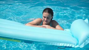 Young girl lying on a mattress in the pool