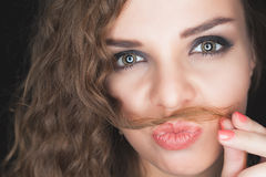 Young pretty girl making mustache of her hair Stock Images