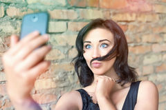 Young pretty girl making selfie of her mustache hair Stock Images
