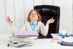 Young pretty girl meditating at working place in office. Stock Image