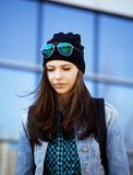 Young pretty girl near business building walking. Student teenager on blue Royalty Free Stock Photo