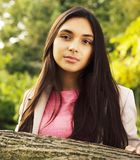 Young pretty girl in park. Young pretty brunette girl in park smiling royalty free stock photo