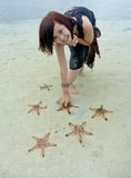 Young pretty girl picks starfish. Young pretty girl pick life star fish on tropical beach during holiday Stock Images