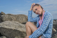 Young pretty girl with pink plaits between rocks Royalty Free Stock Photo