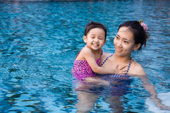 Young pretty girl playing with her mother in pool with clear wat Stock Photo
