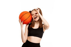 Young pretty girl posing with basketball, isolated on white background. Young emotional pretty girl posing with basketball, isolated on white background. Copy Stock Images