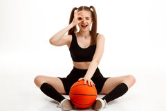 Young pretty girl posing with basketball over white background. Young emotional pretty girl posing with basketball over white background. Copy space Stock Photography