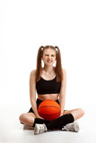 Young pretty girl posing with basketball over white background. Young emotional pretty girl posing with basketball over white background. Copy space Stock Image