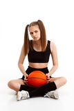 Young pretty girl posing with basketball over white background. Young emotional pretty girl posing with basketball over white background. Copy space Royalty Free Stock Image