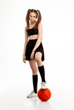 Young pretty girl posing with basketball over white background. Young emotional pretty girl posing with basketball over white background. Copy space Royalty Free Stock Images