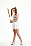 Young pretty girl posing with bat over white background. Young brutal pretty girl posing with bat over white background. Copy space Royalty Free Stock Photo