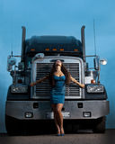 Young pretty girl posing before huge cargo truck Stock Photography