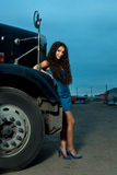 Young pretty girl posing before huge cargo truck Stock Photo