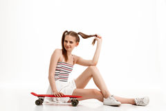 Young pretty girl posing with skateboard over white background. Young emotional pretty girl posing with skateboard over white background. Copy space Royalty Free Stock Images
