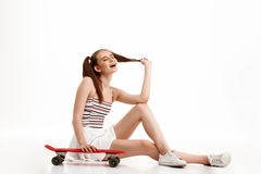 Young pretty girl posing with skateboard over white background. Young emotional pretty girl posing with skateboard over white background. Copy space Royalty Free Stock Photo