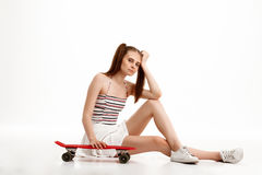 Young pretty girl posing with skateboard over white background. Young emotional pretty girl posing with skateboard over white background. Copy space Stock Photo