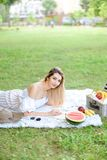 Young pretty girl reading book and lying on plaid near fruits and hat, grass in background. royalty free stock images