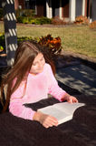Young pretty girl reading a book outdoors. Stock Image
