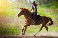 Young pretty girl riding a horse with backlit leaves behind in s Stock Photo