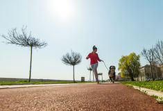 Young pretty girl running outdoor with her Bernese Mountain dog Royalty Free Stock Images