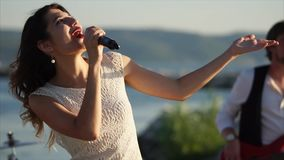 A young and pretty girl sings an energetic song into an outdoor microphone stock footage