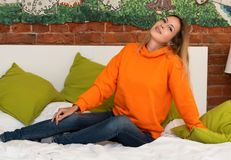A young pretty girl is sitting on a bed in her room in a bright orange hooded sweatshirt or hoody. And blue jeans royalty free stock image