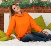 A young pretty girl is sitting on a bed in her room in a bright orange hooded sweatshirt or hoody. And blue jeans stock photography