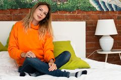 A young pretty girl is sitting on a bed in her room in a bright orange hooded sweatshirt or hoody. And blue jeans royalty free stock images