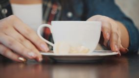 Young pretty girl sitting in a cafe. During this time it is a spoon of cappuccino. Enjoying a pleasant taste of coffee. Young pretty girl sitting in a cafe stock footage