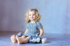 Young pretty girl sitting on a floor. Smiling. Indoor. Toddler girl. Stock Images