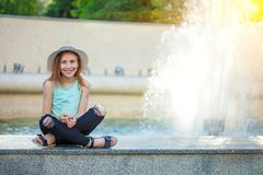 Young pretty girl sitting at a fountain in a straw hat and laughing. royalty free stock image