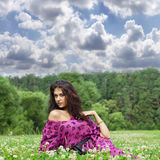 Young pretty girl sitting on green grass Royalty Free Stock Photography