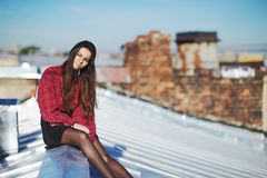 Young pretty girl sitting on a iron roof. Young pretty girl sitting on a iron roof, close-up Stock Photo