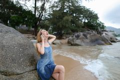 Young pretty girl sitting on sand near sea and stones, talking by smartphone and showing thumbs up. Young pretty girl sitting on sand near sea and stones Stock Photos