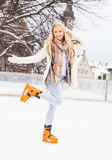 Young and pretty girl skating on an outdoor ice rink Royalty Free Stock Photo