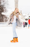 Young and pretty girl skating on an outdoor ice rink Royalty Free Stock Photography