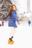 Young and pretty girl skating on an outdoor ice rink Stock Photography
