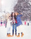 Young and pretty girl skating on outdoor open air ice-rink at wi Stock Images