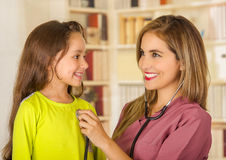 Young pretty girl smiling while a beautiful smiling doctor examining with a stethoscope in her chest in a office Royalty Free Stock Photo