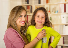 Young pretty girl smiling while a beautiful smiling doctor examining with a stethoscope in her head in a office Royalty Free Stock Images